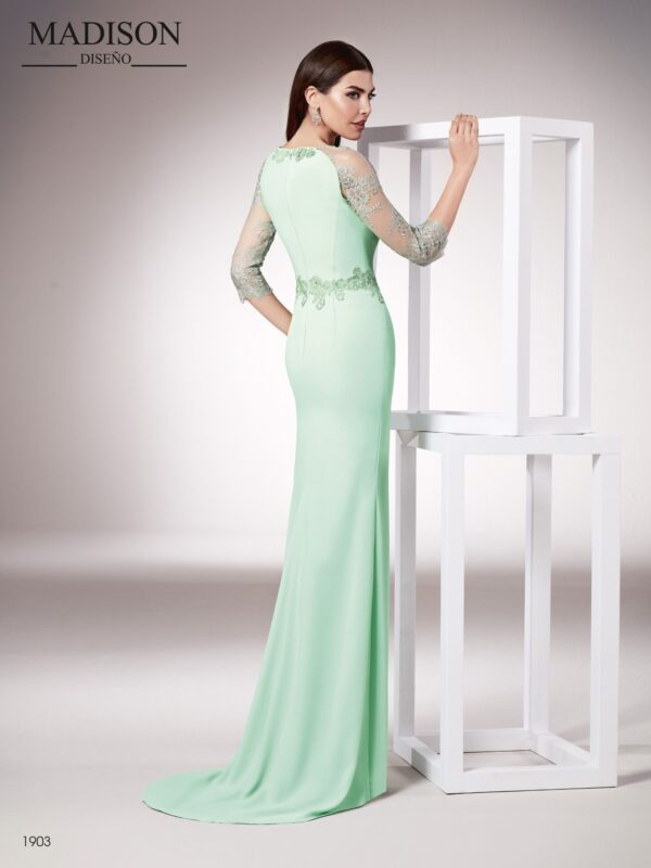 Vestido realizado en crepe y un elegante tul bordado con pasamaneria rodeando la cintura y el escote, tanto trasero como delantero.